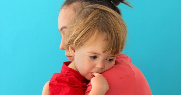 Vista lateral de la mamá joven que abraza al niño triste con el dedo en la boca que mira abajo aislado en azul