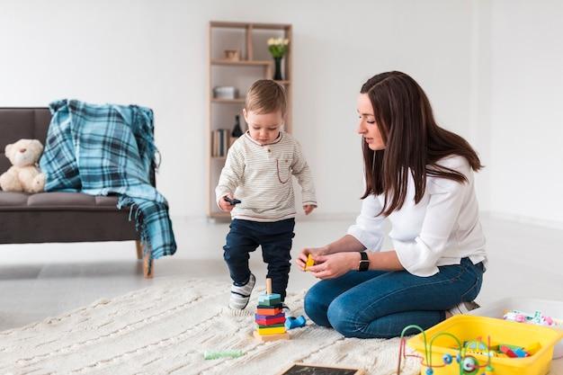 Vista lateral de mamá jugando con un niño en casa