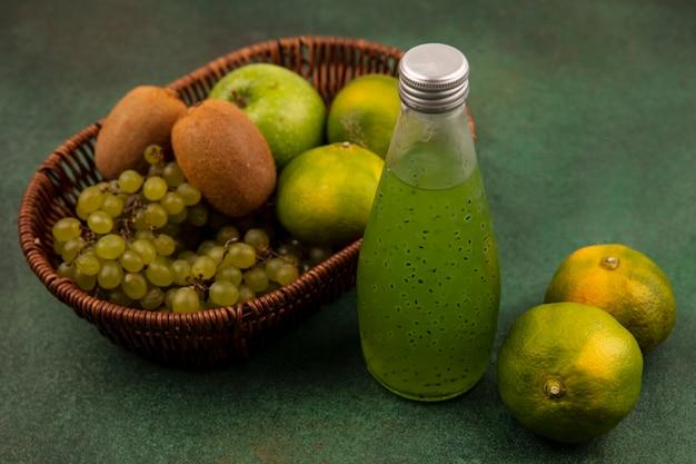 Vista lateral de mandarinas verdes con manzana, kiwi y uvas en una canasta con una botella de jugo en una pared verde