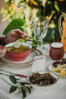 Vista lateral de la mano femenina con una cuchara de sopa de albóndigas dushbara