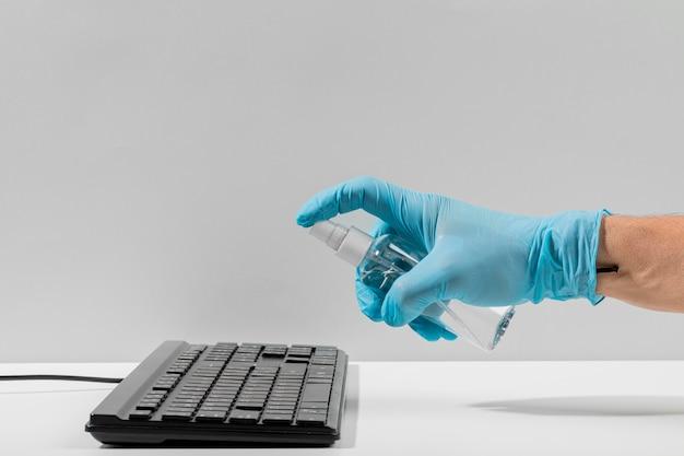 Vista lateral de la mano con guante quirúrgico desinfectando el teclado