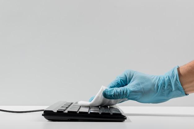 Vista lateral de la mano con guante quirúrgico que desinfecta el teclado con espacio de copia