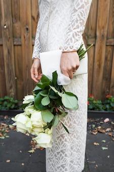 Vista lateral de la mano de la novia con ramo de rosas blancas y embrague
