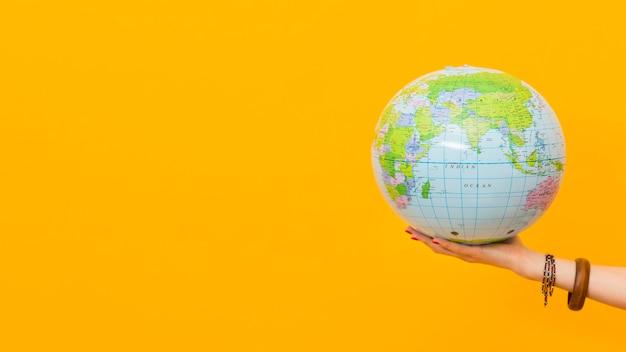 Vista lateral de la mano que sostiene el globo con espacio de copia