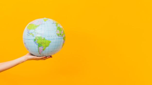 Vista lateral de la mano que sostiene el globo terrestre con espacio de copia