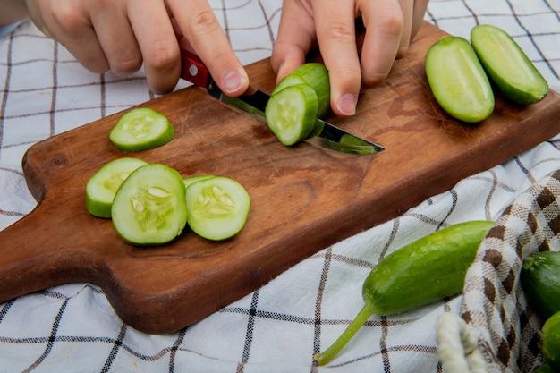 Vista lateral de las manos cortando pepino con un cuchillo en la tabla de cortar con unos enteros en la canasta sobre una superficie de tela escocesa