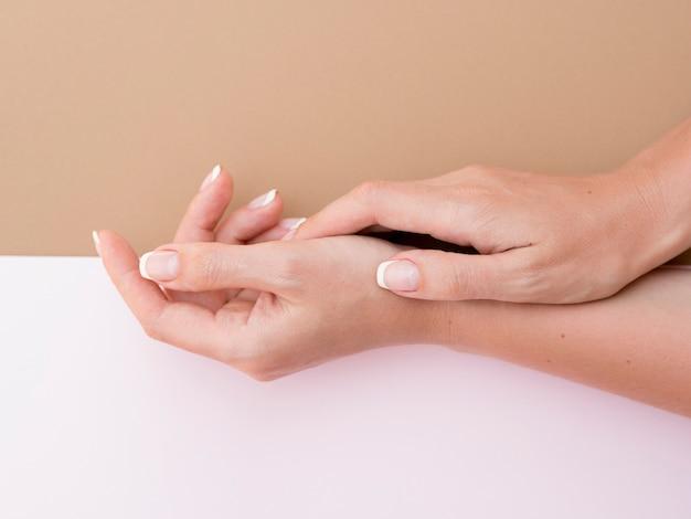 Vista lateral de las manos cuidadas de la mujer.