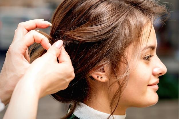 Vista lateral de las manos del estilista peinar el cabello de la hermosa joven morena caucásica en un salón de belleza