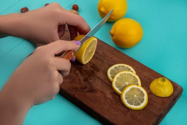 Vista lateral de las manos femeninas rebanar limón con un cuchillo en la tabla de cortar y nueces con limones sobre fondo azul.