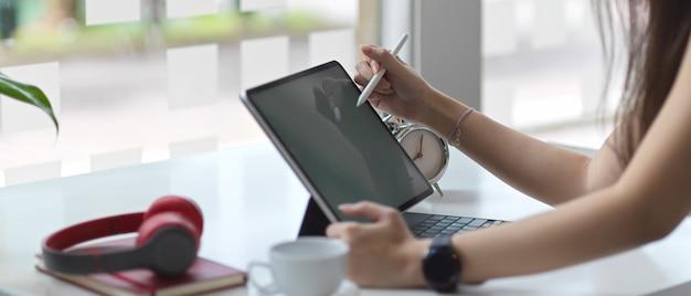 Vista lateral de manos femeninas con tableta digital en mesa blanca en espacio de trabajo co