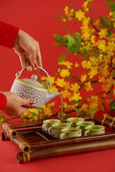 Vista lateral de manos femeninas vertiendo té verde sobre fondo rojo.