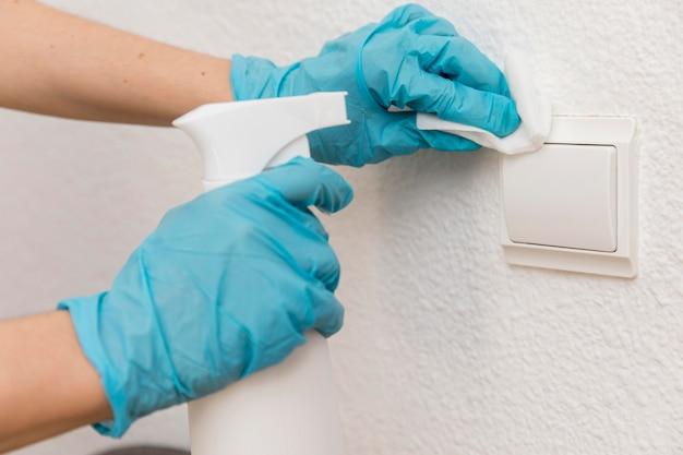 Vista lateral de manos con guantes quirúrgicos que desinfectan el interruptor de la luz