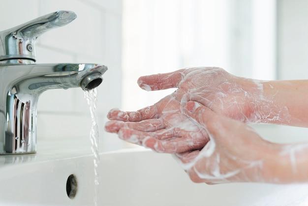 Vista lateral de manos jabonosas en el fregadero