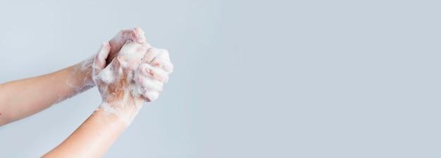 Vista lateral de manos jabonosas que se lavan con espacio de copia