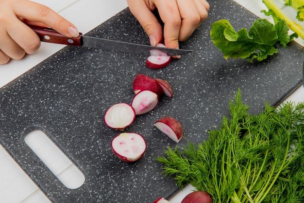 Vista lateral de manos de mujer cortando rábano con cuchillo en la tabla de cortar y montón de eneldo sobre fondo de madera