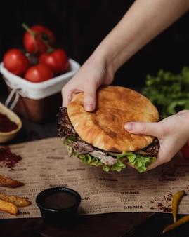 Vista lateral de manos sosteniendo doner kebab en pan de pita