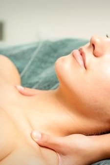Vista lateral de las manos de la terapeuta femenina haciendo masaje de cuello y hombros a la joven mujer caucásica en el salón de belleza spa