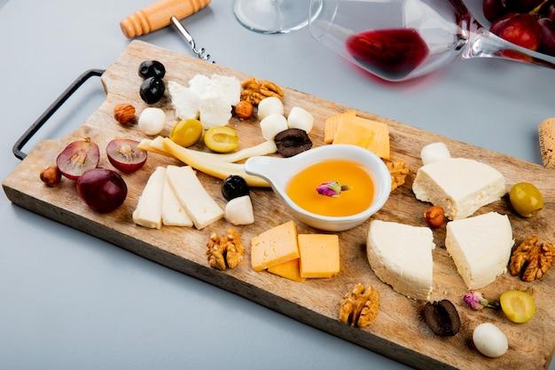 Vista lateral de la mantequilla derretida con diferentes tipos de queso uva nueces de oliva en la tabla de cortar y mentir copa de vino en blanco