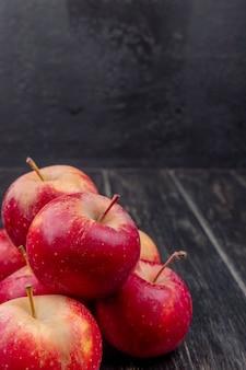 Vista lateral de manzanas rojas sobre superficie de madera y superficie negra con espacio de copia