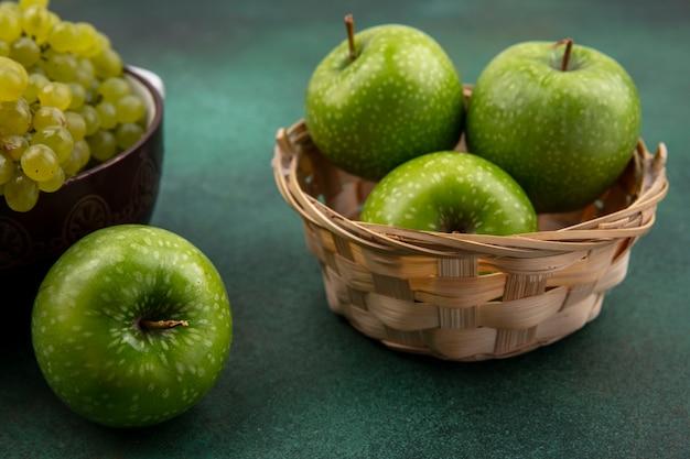 Vista lateral de manzanas verdes en una canasta con uvas verdes sobre un fondo verde