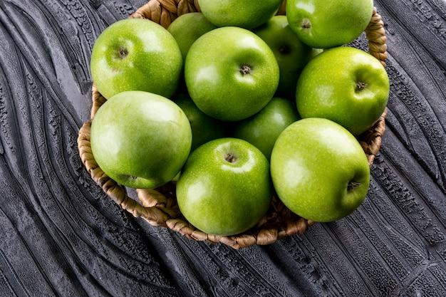 Vista lateral de manzanas verdes en cesta de paja beige