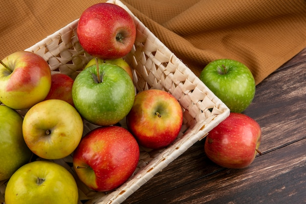 Vista lateral de manzanas verdes y rojas en una cesta sobre una toalla marrón sobre un fondo de madera