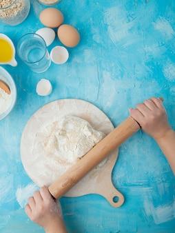 Vista lateral de la masa de amasar de la mano de la mujer en la tabla de amasar con rodillo y huevos de agua sobre fondo azul con espacio de copia
