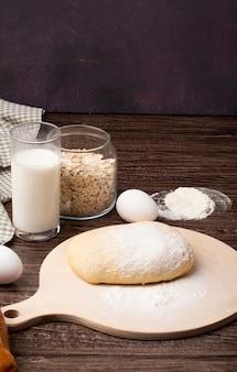 Vista lateral de la masa y la harina en la tabla de cortar con copos de avena con leche y huevo sobre superficie de madera y fondo marrón con espacio de copia