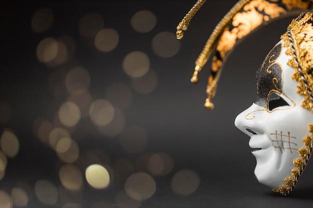 Vista lateral de la máscara para carnaval con brillo y espacio de copia.