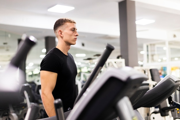 Vista lateral masculino joven en el entrenamiento de gimnasio