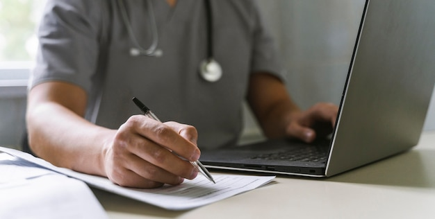 Vista lateral del médico con estetoscopio trabajando en una computadora portátil y escribiendo en papel