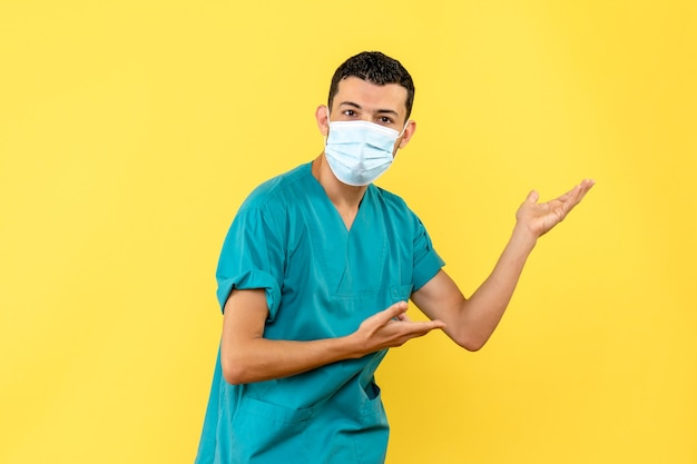 Vista lateral de un médico con máscara un médico habla sobre la importancia de lavarse las manos durante una pandemia