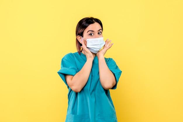 Vista lateral de un médico con máscara, un médico con máscara está hablando de pacientes con covid