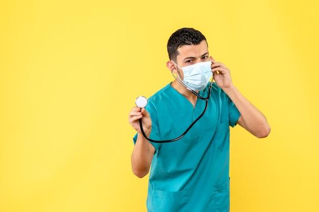 Vista lateral de un médico un médico en máscara con fonendoscopio habla con pacientes