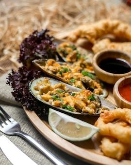 Vista lateral mejillones de mariscos con salsas de calamar y una rodaja de limón
