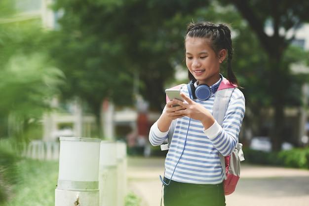 Vista lateral del mensaje de texto de una niña asiática a sus padres después de la escuela de pie al aire libre en un agradable día de primavera