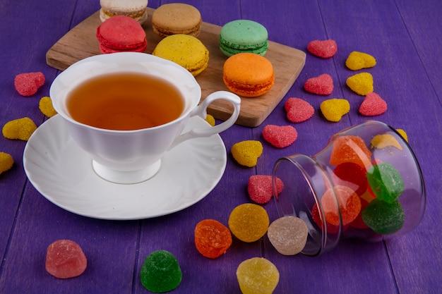 Vista lateral de mermeladas derramando de jarra y taza de té en platillo con sándwiches de galletas en la tabla de cortar y fondo morado