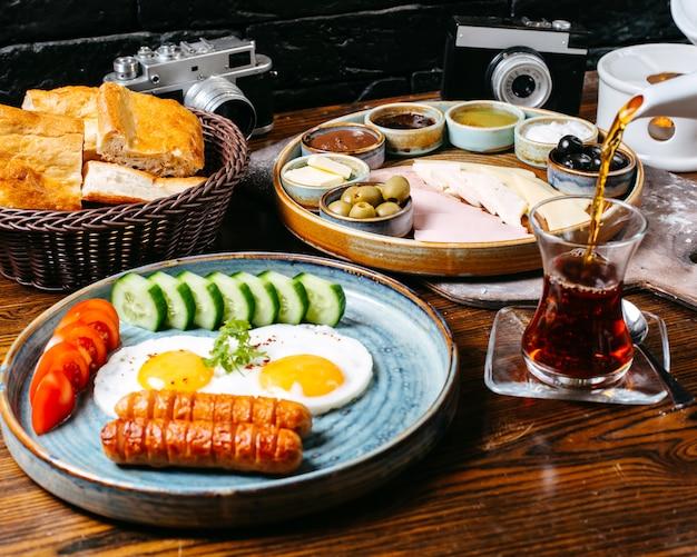 Vista lateral de la mesa de desayuno con huevo frito y salchichas queso jamón y verduras