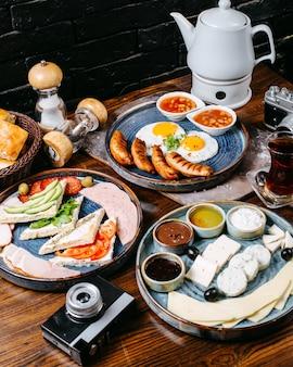 Vista lateral de la mesa de desayuno con huevo frito y salchichas verduras frescas queso y jamón