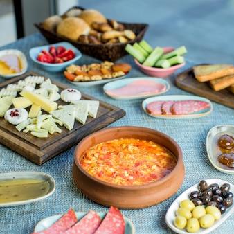 Vista lateral de la mesa de desayuno servido con varios alimentos huevos fritos con tomate salchichas queso ensalada fresca postre y té