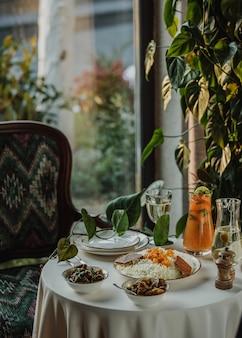 Vista lateral de una mesa servida con pilaf con frutos secos servidos y carne guisada con hierbas en tazones