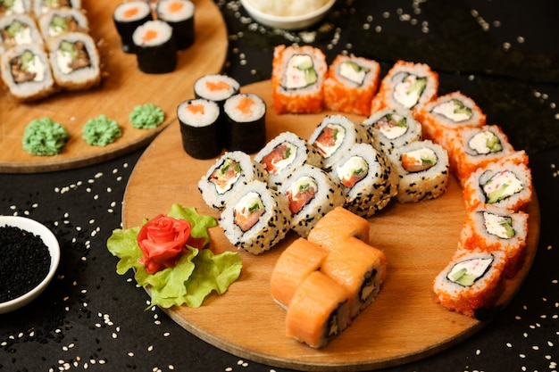 Vista lateral mezclar rollos de sushi en una bandeja con jengibre y wasabi