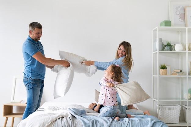 Vista lateral de miembros de la familia peleando con almohadas