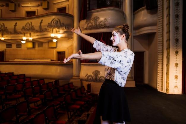Vista lateral del mimo femenino ensayando en el escenario