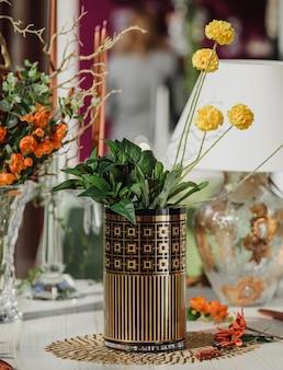 Vista lateral del moderno jarrón de vidrio con estampado geométrico con flores amarillas en una mesa de madera