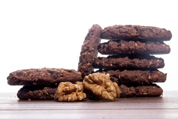 Vista lateral de un montón de galletas de chispas de chocolate con cereales, nueces y cacao sobre la mesa