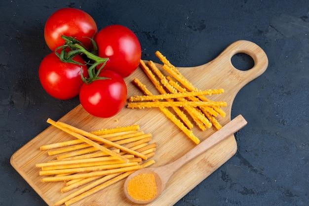 Vista lateral de un montón de tomates frescos con palitos de pan con sal esparcidos sobre una tabla para cortar madera en negro