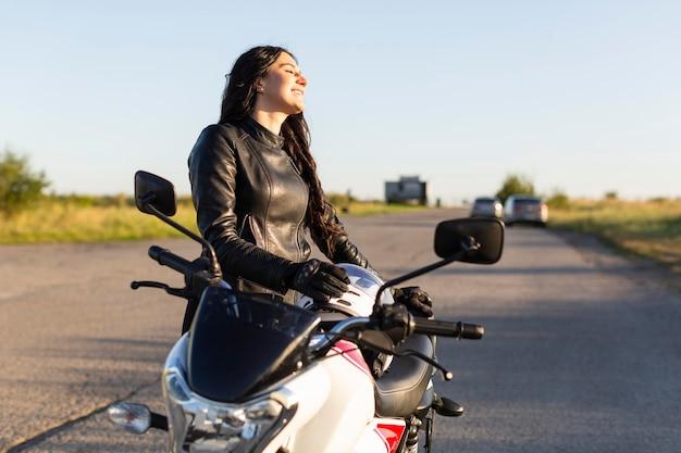 Vista lateral del motociclista femenino admirando la puesta de sol