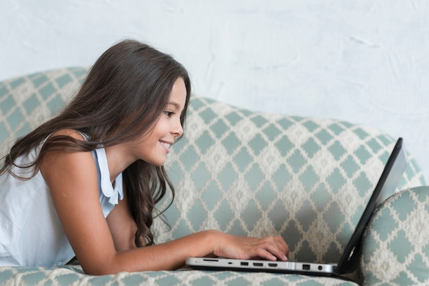 Vista lateral de una muchacha bonita que usa la computadora portátil en el sofá