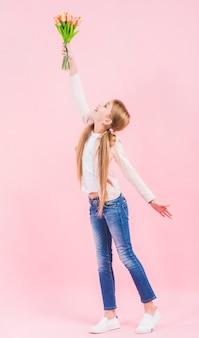 La vista lateral de una muchacha que levanta su mano que sostiene el tulipán florece en la mano que se opone a fondo rosado